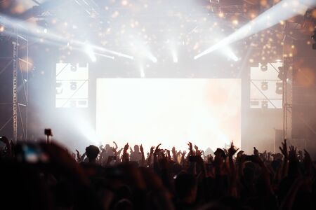 Photo pour Stage lights and crowd of audience with hands raised at a music festival. Fans enjoying the party vibes. - image libre de droit