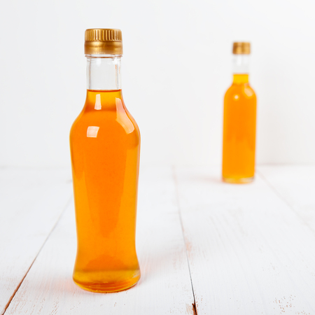 Photo pour Two glass bottles with homemade orange syrup - image libre de droit