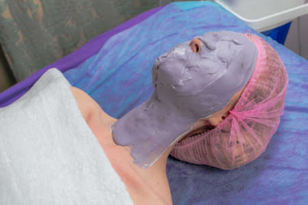 Closeup Alginate Peel Off Powder facial Mask in Beauty salon. Beautiful young woman with facial mask at woman face at beauty salon. Beautiful young woman with facial mask in spa salon indoors.