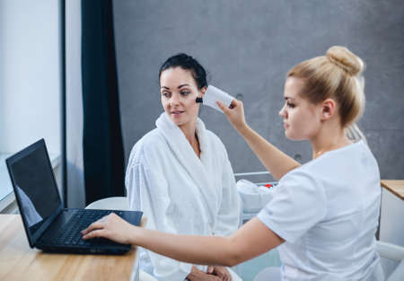 Photo pour Female doctor and patient during examination of facial skin. The results of the skin condition are shown on the laptop. - image libre de droit
