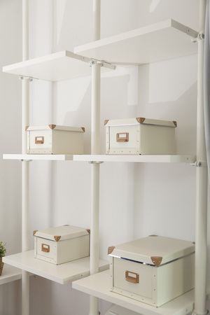 white closed boxes for home organizer arranged on shelf in room