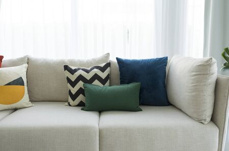 Photo pour Large white sofa with colorful cushions in a spacious living room interior with green plants and white walls. - image libre de droit