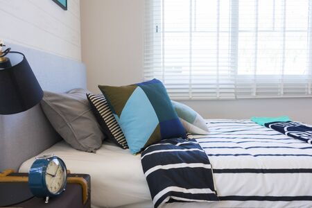 Photo pour Graphic blue pattern pillow on bed in boy bedroom. - image libre de droit