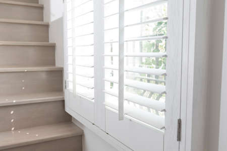 Photo pour Closeup view of window with horizontal blinds. White Roller Blinds or Louver curtains at the glass window - image libre de droit