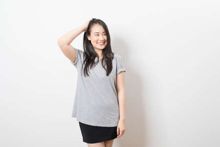 Photo pour Portrait of happy young asian woman wearing grey shirt smiling at camera while standing over white background. - image libre de droit