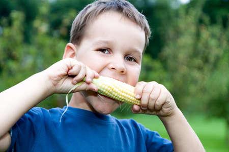 Foto für boy eating young corn outdoors - Lizenzfreies Bild