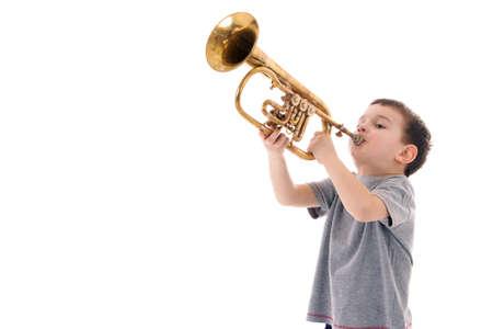 Photo pour young boy blowing into a trumpet against white background - image libre de droit