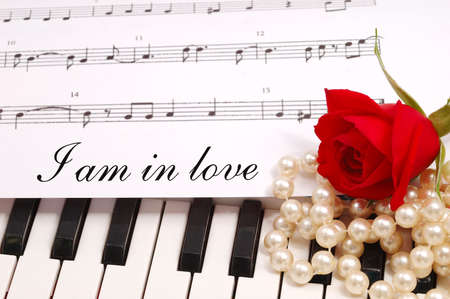 Photo pour red silky rose with musical notes and a piano - image libre de droit