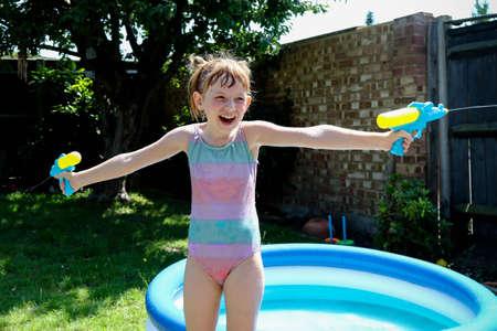 Foto de Preteen caucasian girl playing wth water guns on a hot summer's day - Imagen libre de derechos