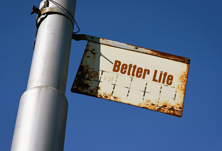 Text Better Life written on a white metal board