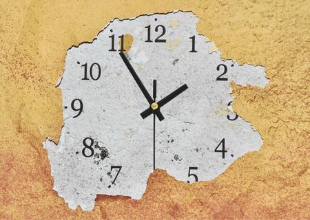 Photo pour Big clock on a yellow peeling wall showing the time - image libre de droit