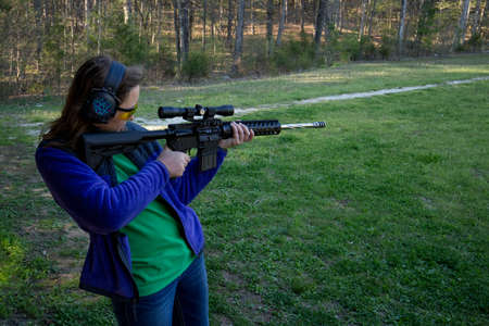 Teenage Girl at shooting range firing an AR-15 rifle.