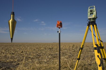 Total station, prism and plumb-bob in the field.