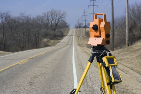 Theodolite set on the edge of road - spring land surveying.