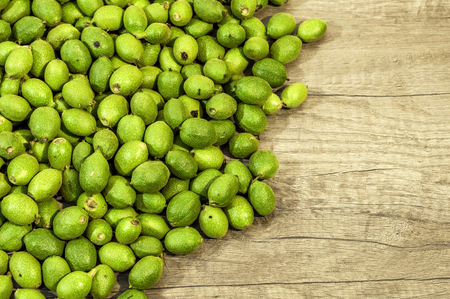 Photo pour A lot green young walnuts in husks on wooden table - image libre de droit
