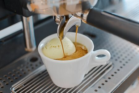 Photo pour Affogato coffee with ice cream on a ceramic cup with coffee pouring from espresso machine - image libre de droit
