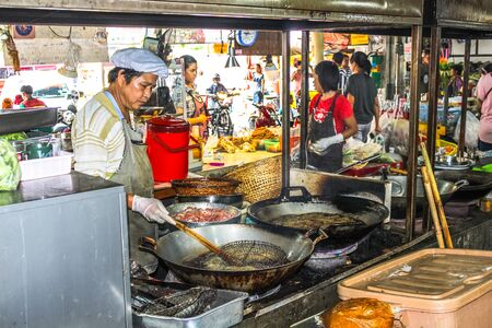 Chiang Mai, Thailand - July 23, 2011: Man cooking food on the street, market