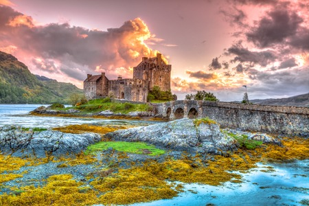 Eilean Donan Castle at sunset, Dornie, Kyle of Lochalsh in Scotland, United Kingdom. It is the most visited castle, situated on an island at the confluence of three sea lochs.