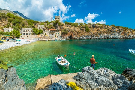 A fisherman fishing in the spectacular bay of Alypa Beach with a transparent blue sea, Mania Peninsula, Lakonia, Peloponnese, Greece on a sunny day.