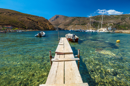 Wooden jetty with fishing boats in the clear tropical waters of Porto Kagio, Mani Peninsula, Lakonia, Peloponnese, Greece.