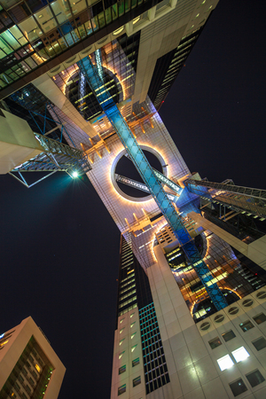 Osaka, Japan - April 28, 2017: bottom view of Lumi Sky Walk, the panoramic corridor joining the two towers of Floating Garden Observatory in Umeda Sky Building by night.