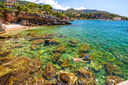 Woman snorkeling in Foneas Beach, Kardamili, Peloponnese. Female bikini snorkeling around the rocks in summer. Woman snorkeler swims in crystal water. Nature scenic landscape in Mani Peninsula, Greece