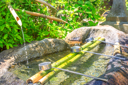 Close up of Japanese bamboo fountain and ladles used for washing hands. Purification fountain with ladles at a Buddhist temple. Hase-dera in Kamakura, Japan. Japanese culture concept.