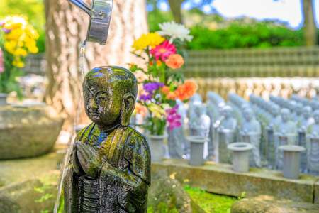 Worshiping at Jizo Statue. Ladle pouring water on Jizos head. Hase-dera Temple in Kamakura, Japan. Japanese culture concept.
