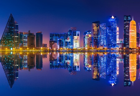 Photo pour Doha West Bay skyline lighting by night reflecting in Doha Bay. Modern skyscrapers of Doha in Qatar, Middle East, Arabian Peninsula in Persian Gulf. Night urban scene. - image libre de droit