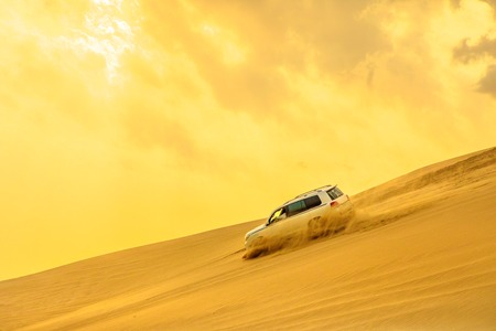 Photo pour Dune Bashing at sunset sky near Qatar and Saudi Arabia. Khor Al Udeid, Persian Gulf, Middle East. Inland sea is a major tourist destination for Qatar. Discovery and adventure travel concept. - image libre de droit