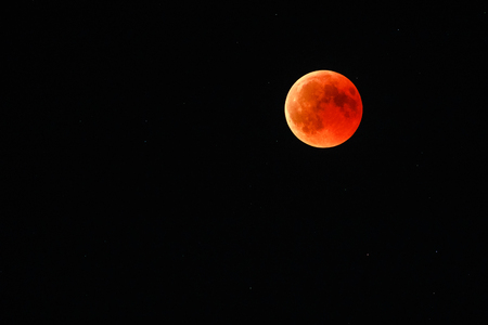 Photo for Astronomical background. Closeup of full red moon over dark black sky. The total phase of lunar eclipse on July 27, 2018. Moon turning red cause of closer Mars planet to the moons surface. - Royalty Free Image