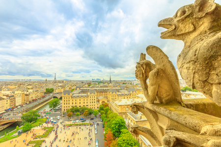 Foto de The gargoyles of Notre Dame cathedral from aerial view on Paris skyline. Paris city capital of France. Top view of the gothic church Our Lady of Paris, Eiffel Tower on the horizon. - Imagen libre de derechos