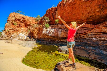 Photo pour Carefree woman enjoying after Ormiston Pound Walk, a circuit that follows the rocky slope into of pound and back along the gorge by main waterhole. West MacDonnell Range, Australia, Northern Territory - image libre de droit
