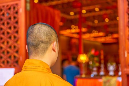 Photo pour Hong Kong, China - December 11, 2016: monk in orange from behind inside the Po Lin Monastery of the Big Buddha, symbol of Lantau Island, Chinese destination. - image libre de droit
