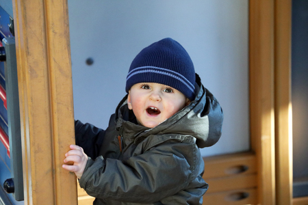 Foto de Close Up Portrait Of Cute Baby Boy Wearing A Blue Knit Winter Hat And Green Winter Parka - Imagen libre de derechos