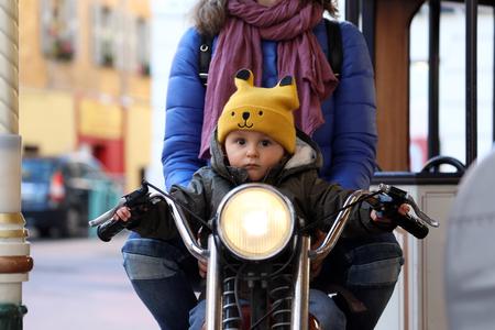 Foto de Cute Baby Boy Sitting On A Vintage Motorcycle With His Mom, The Little Boy On The Carousel, Close Up Portrait - Imagen libre de derechos