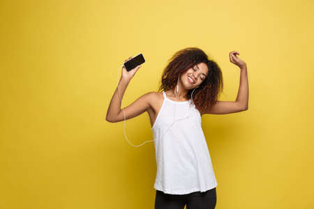 Photo pour Lifestyle Concept - Portrait of beautiful African American woman joyful listening to music on mobile phone. Yellow pastel studio background. Copy Space. - image libre de droit