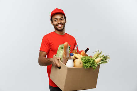 Photo pour Delivery Concept - Handsome African American delivery man carrying package box of grocery food and drink from store. Isolated on Grey studio Background. Copy Space. - image libre de droit