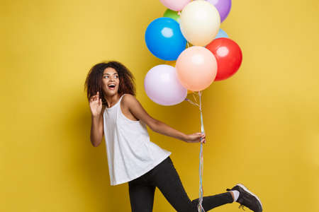 Foto de Celebration Concept - Close up Portrait happy young beautiful african woman with white t-shirt running with colorful party balloon. Yellow Pastel studio Background - Imagen libre de derechos