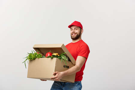 Photo pour Delivery Concept - Handsome Cacasian delivery man carrying package box of grocery food and drink from store. Isolated on Grey studio Background. Copy Space. - image libre de droit