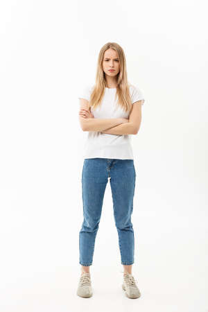 Foto de Full length portrait of a pretty young caucasian woman wearing jean and looking upset with her arms crossed - Imagen libre de derechos