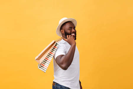 Photo pour Happy african american man holding shopping bags on yellow background. Holidays concept - image libre de droit