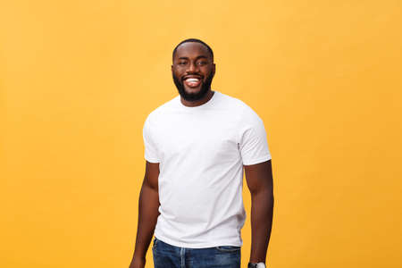 Foto de Portrait of delighted African American male with positive smile, white perfect teeth, looks happily at camera, being successful enterpreneur, wears white t shirt. - Imagen libre de derechos