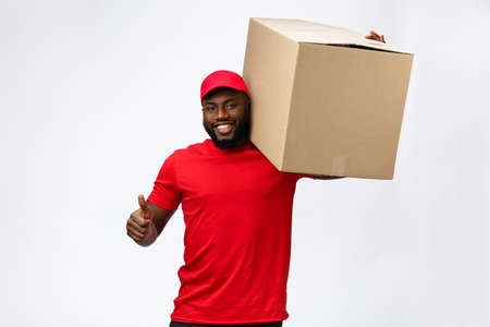 Photo pour Delivery Concept - Handsome African American delivery man carrying package box. Isolated on Grey studio Background. Copy Space - image libre de droit