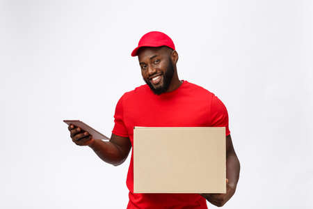 Photo pour Delivery Concept - Portrait of Handsome African American delivery man or courier showing a confirmation document form to sign. Isolated on Grey studio Background. Copy Space - image libre de droit