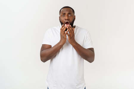 Photo pour Portrait of shocked young African American man wearing white blank T-shirt looking at the camera in surprise, stunned with some incredible story. - image libre de droit