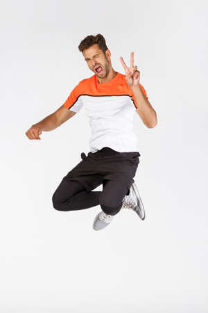 Photo pour Cheeky, happy attractive young bearded masculine sportsman in activewear, jumping and showing peace sign in air, wink joyfully, express positivity, enjoy working out and do sports, white background - image libre de droit