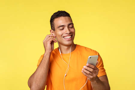 Foto de Cheerful smiling masculine young man in orange t-shirt, holding smartphone, chatting as listening music or watching video in headphones, got voice message and laughing over it, yellow background - Imagen libre de derechos