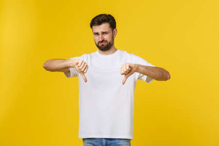 Photo pour Young handsome man wearing white t-shirt over isolated background Doing thumbs down, disagreement and agreement expression. Crazy conflict. - image libre de droit