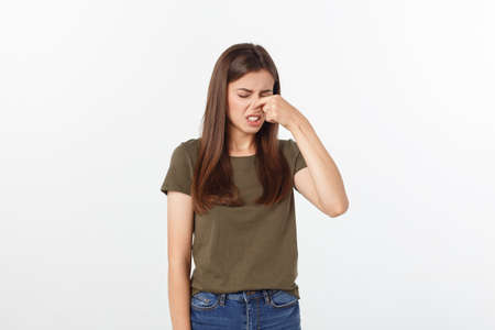 Photo pour disgusted young blonde closing her nose with her fingers. Isolated over white background. - image libre de droit